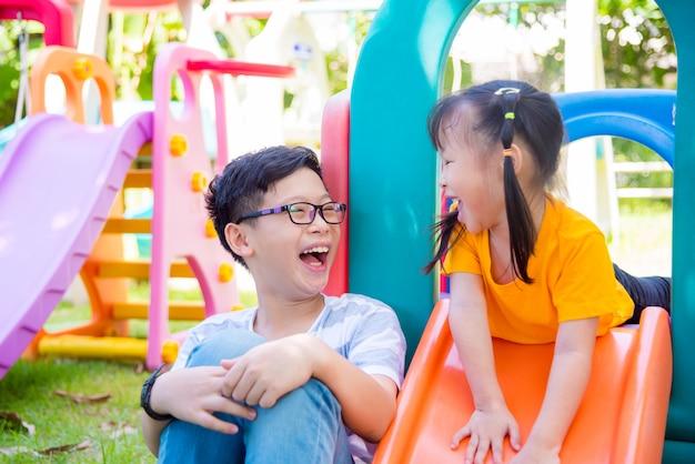 Giovane ragazzo asiatico che gioca con sua sorella al campo da giuoco