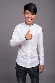 Giovane ragazzo asiatico che indossa abiti casual intelligenti contro il muro grigio