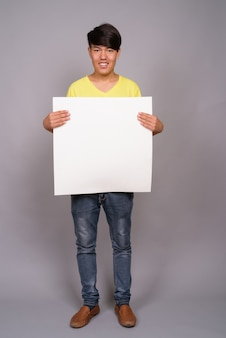Giovane ragazzo asiatico che indossa camicia gialla contro il muro grigio