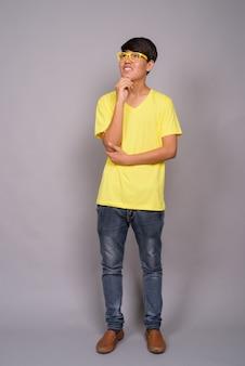 Giovane ragazzo asiatico che indossa camicia gialla e occhiali da vista contro il muro grigio
