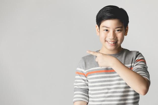 Giovane ragazzo asiatico che pensa e che indica mentre sorridendo con lo spazio della copia.