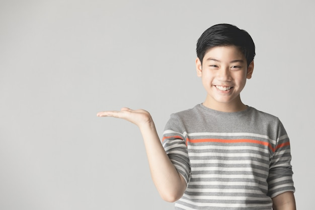 Giovane ragazzo asiatico che pensa e che mostra mentre sorridendo con lo spazio della copia.