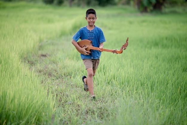 Giovane ragazzo asiatico con la chitarra fatta a mano all'aperto, paese di vita