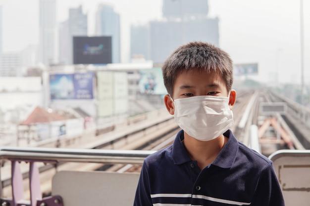 Giovane ragazzo asiatico del preteen che indossa maschera di protezione medica, scoppio del coronavirus di wuhan, inquinamento atmosferico di pm 2.5 e concetto di salute