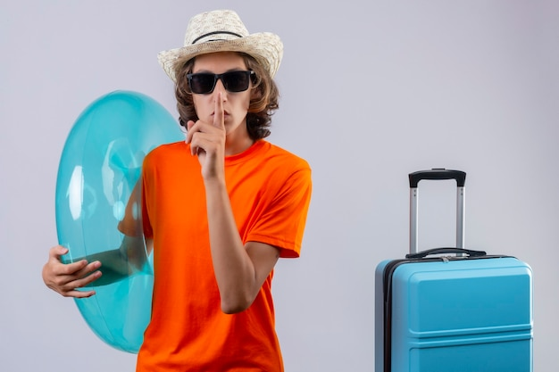 Giovane ragazzo bello in maglietta arancione che indossa occhiali da sole neri che tengono anello gonfiabile che fa gesto di silenzio con il dito sulle labbra in piedi con la valigia di viaggio sopra priorità bassa bianca