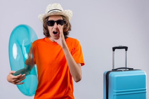 Giovane ragazzo bello in maglietta arancione che indossa occhiali da sole neri che tengono l'anello gonfiabile gridando felice e positivo o chiamando qualcuno con la mano vicino alla bocca che sta con la valigia di viaggio sopra briciolo