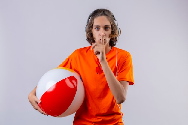 Giovane ragazzo bello in maglietta arancione con le cuffie che tengono palla gonfiabile che fa gesto di silenzio con il dito sulle labbra in piedi sopra priorità bassa bianca