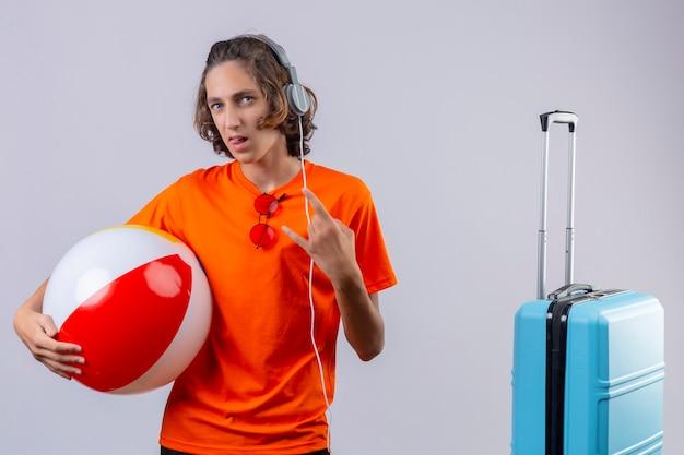 Giovane ragazzo bello in maglietta arancione con le cuffie che tengono palla gonfiabile che fa simbolo della roccia che sembra in piedi sicuro vicino alla valigia di viaggio sopra fondo bianco