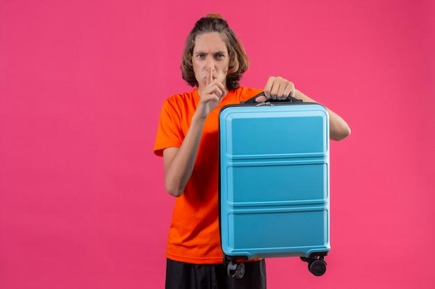 Giovane ragazzo bello in maglietta arancione in piedi con la valigia da viaggio che fa gesto di silenzio con il dito sulle labbra su sfondo rosa