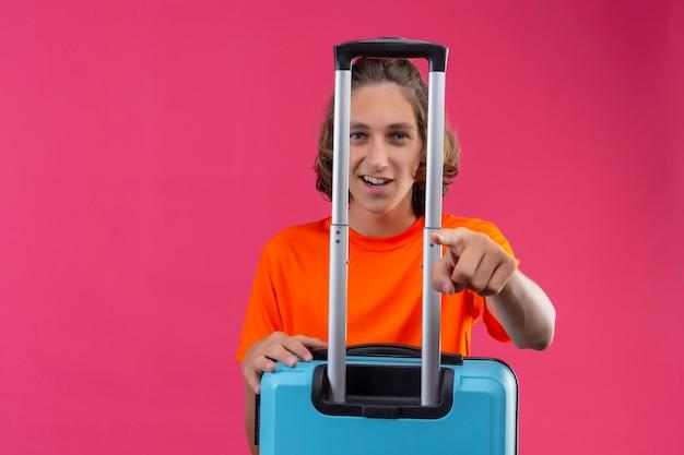Giovane ragazzo bello in maglietta arancione in piedi con la valigia da viaggio che punta con il dito alla fotocamera sorridente con la faccia felice su sfondo rosa