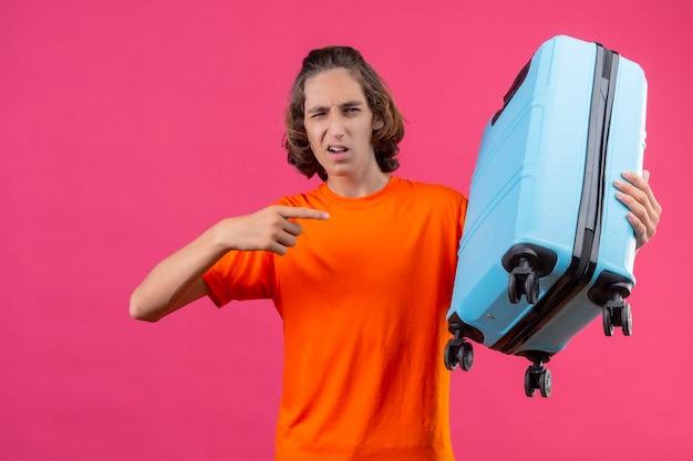Giovane ragazzo bello in maglietta arancione in piedi con la valigia da viaggio che punta con il dito ammiccante guardando fiducioso su sfondo rosa