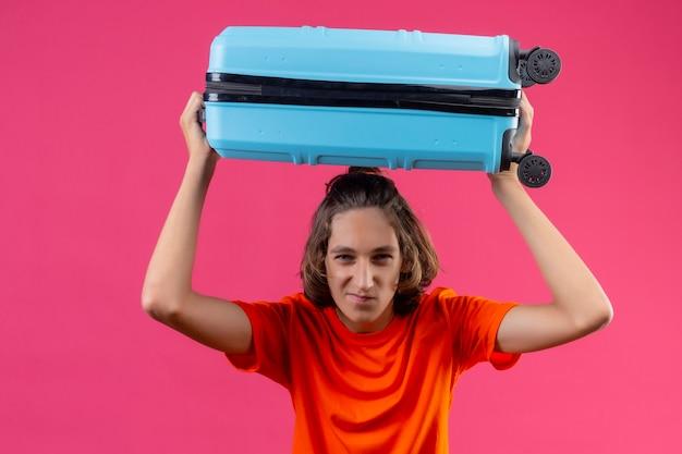 Giovane ragazzo bello in maglietta arancione in piedi con la valigia di viaggio sulla testa che guarda l'obbiettivo con sorriso su sfondo rosa