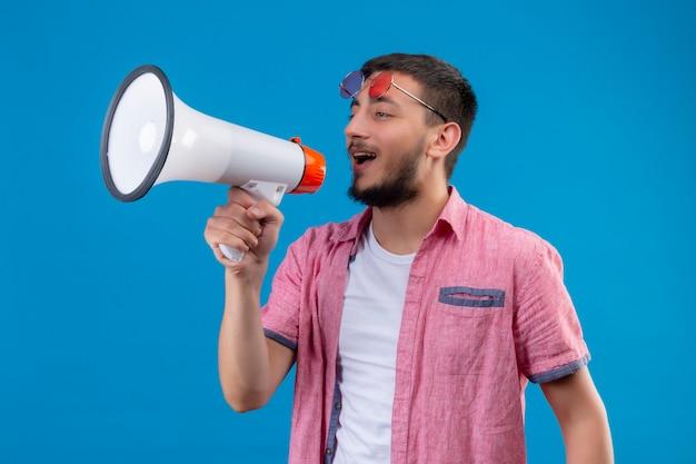 Giovane ragazzo bello viaggiatore che parla al megafono con il viso felice in piedi su sfondo blu