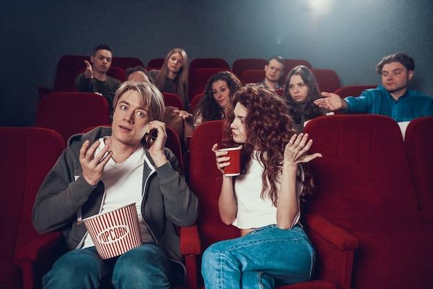 Giovane ragazzo biondo parla al telefono durante lo spettacolo cinematografico.