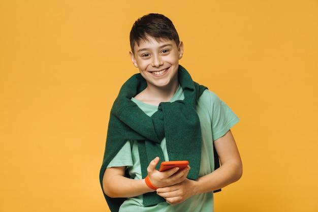 Giovane ragazzo carino caucasico, ampio sorriso splendente, indossa camicia verde chiaro, tiene i modelli di telefono cellulare sul muro giallo. concetto di persone positive. le vacanze sono iniziate