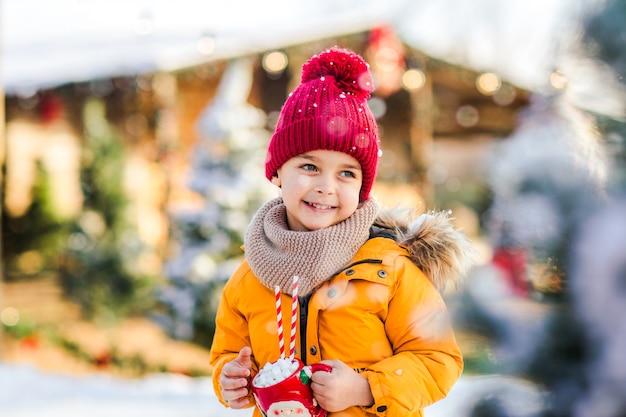 Giovane ragazzo carino in una giacca arancione sulla pista di pattinaggio