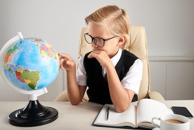 Giovane ragazzo caucasico che si siede nella sedia esecutiva in ufficio e che esamina il globo della terra