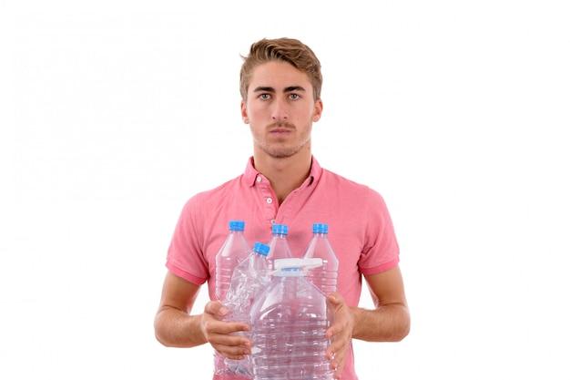 Giovane ragazzo caucasico con un sacchetto e bottiglie di plastica da riciclare