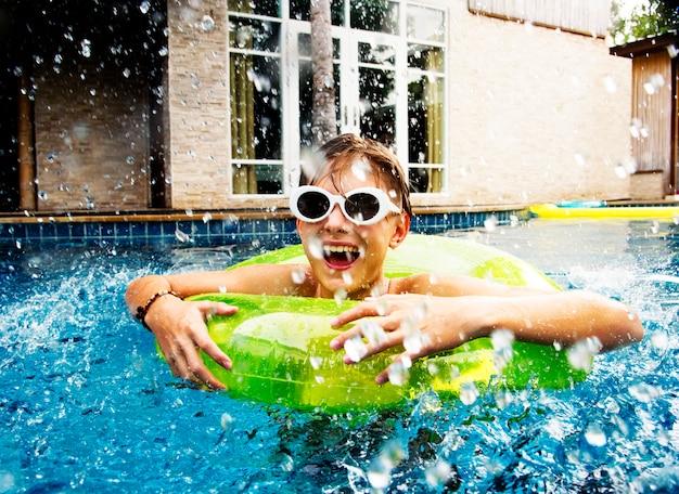 Giovane ragazzo caucasico godendo di galleggiamento in piscina con tubo