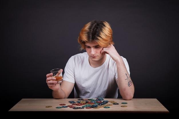 Giovane ragazzo che beve whisky e guardando le fiches da poker