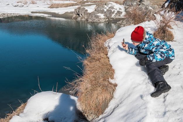 Giovane ragazzo che cattura le foto sul fiume della costa