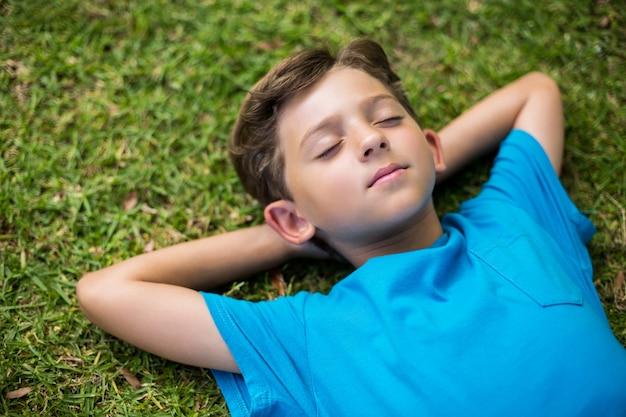 Giovane ragazzo che dorme nel parco