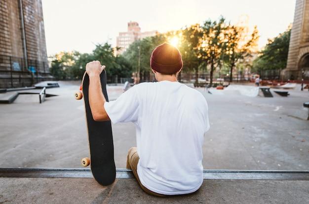 Giovane ragazzo che esegue trucchi con lo skateboard in uno skate park