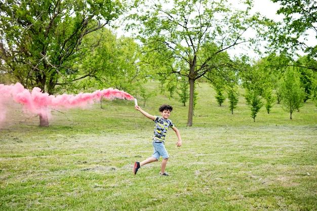 Giovane ragazzo che funziona con un chiarore rosa