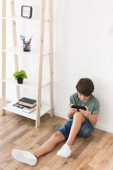 Giovane ragazzo che gioca su smartphone