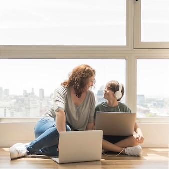 Giovane ragazzo che gioca sul computer portatile accanto alla mamma