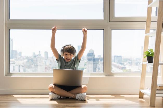 Giovane ragazzo che gioca sul computer portatile