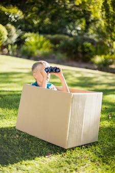 Giovane ragazzo che guarda tramite il binocolo in parco