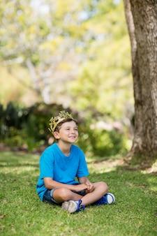 Giovane ragazzo che indossa una corona e seduto sull'erba