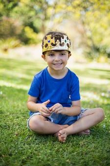 Giovane ragazzo che indossa una corona e sorridente