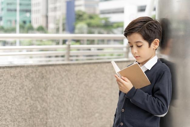 Giovane ragazzo che legge un libro sul distretto aziendale urbano, concetto di istruzione