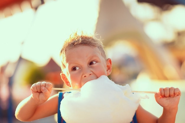 Giovane ragazzo che mangia zucchero filato