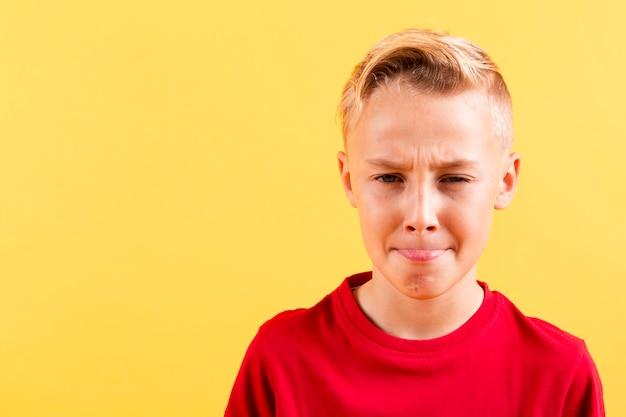 Giovane ragazzo che mostra lingua con copia-spazio