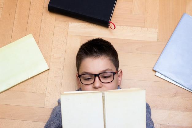 Giovane ragazzo che si trova sul pavimento tra i libri e la lettura di un libro, ragazzo che studia i compiti a casa.