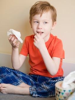 Giovane ragazzo che soffia il naso