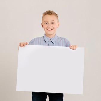 Giovane ragazzo che tiene carta in bianco