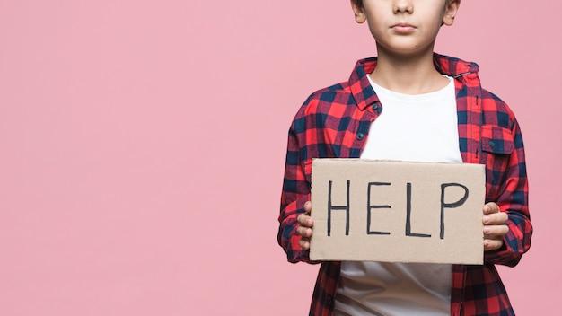 Giovane ragazzo che tiene cartone con messaggio di aiuto