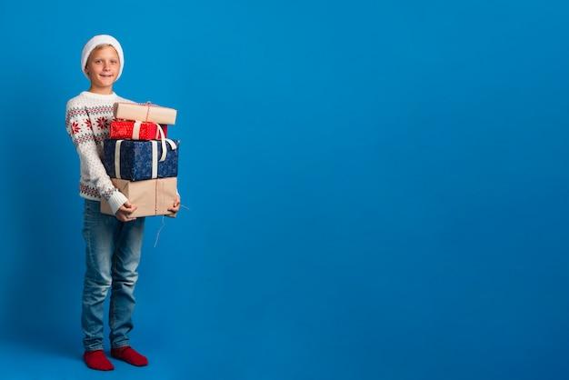 Giovane ragazzo che tiene il mucchio di regali