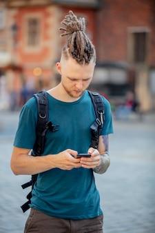 Giovane ragazzo con i dreadlocks sta camminando con un telefono per strada