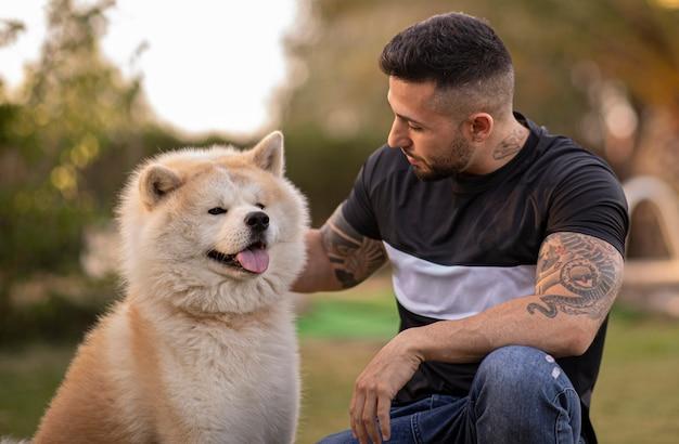 Giovane ragazzo con i tatuaggi che sorride felice con il suo cane