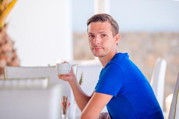 Giovane ragazzo con la bevanda all'aperto nel giorno caldo