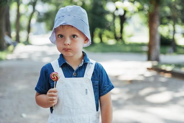 Giovane ragazzo con lecca-lecca colorato