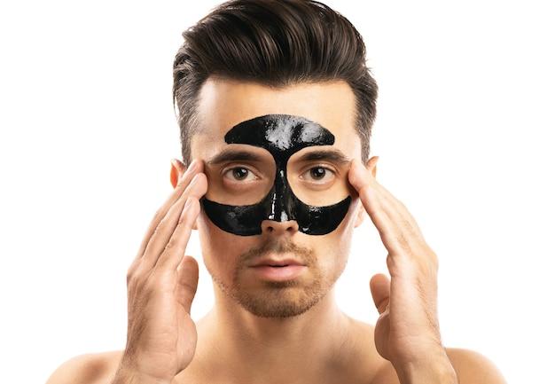 Giovane ragazzo con una maschera nera del carbone sul suo fronte su bianco.