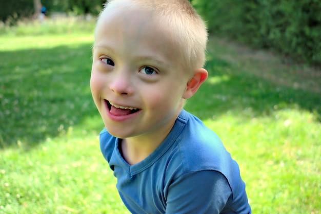 Giovane ragazzo con una sindrome di down che sta giocando in un parco