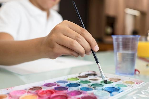 Giovane ragazzo del primo piano che dipinge a casa