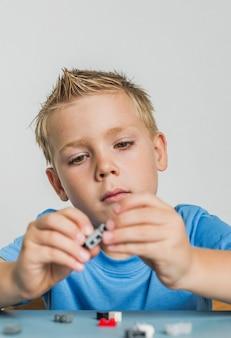 Giovane ragazzo del primo piano che gioca con il lego